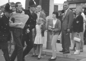 Holiday makers watch as a young man is escorted away.
